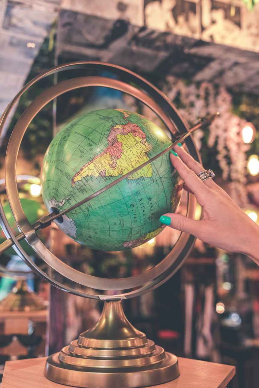 woman hand touches green desk globe